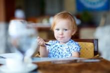 Une toute petite fille en train de manger.