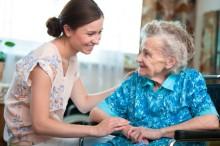 Une jeune femme prend soin d'une personne âgée.