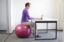 une homme travaille sur ordinateur assis sur une boule