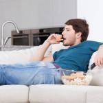 Un homme regarde la télévision en mangeant