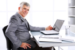 un senior travaille sur ordinateur
